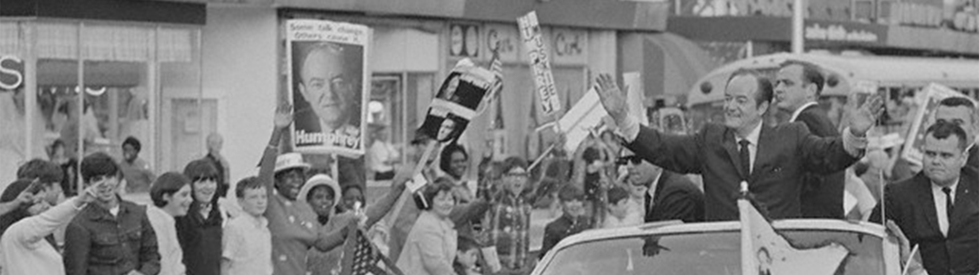 Hubert H. Humphrey rides in a car past people in support of his 1968 presidential campaign
