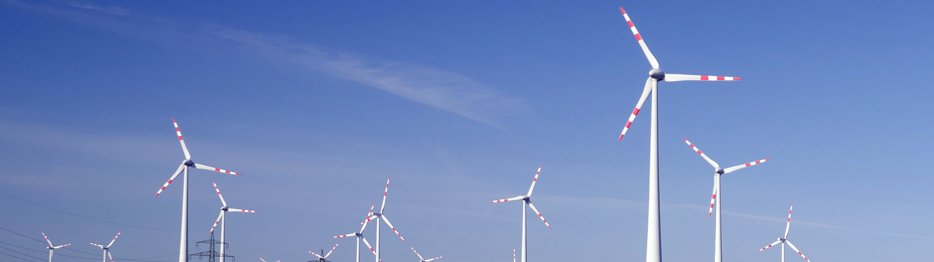 Long shot of several white wind turbines set against a blue sky
