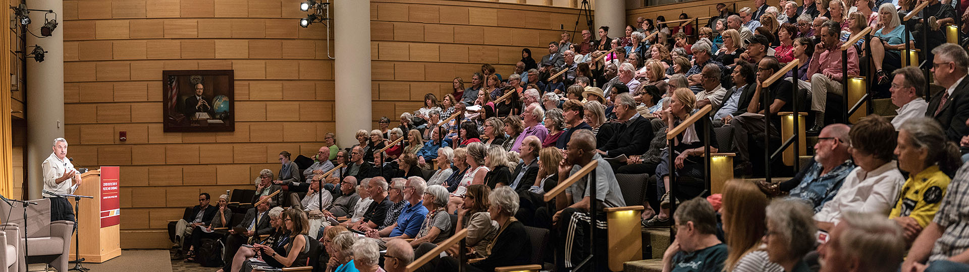Wide shot of a large audience in the Humphrey School's auditorium