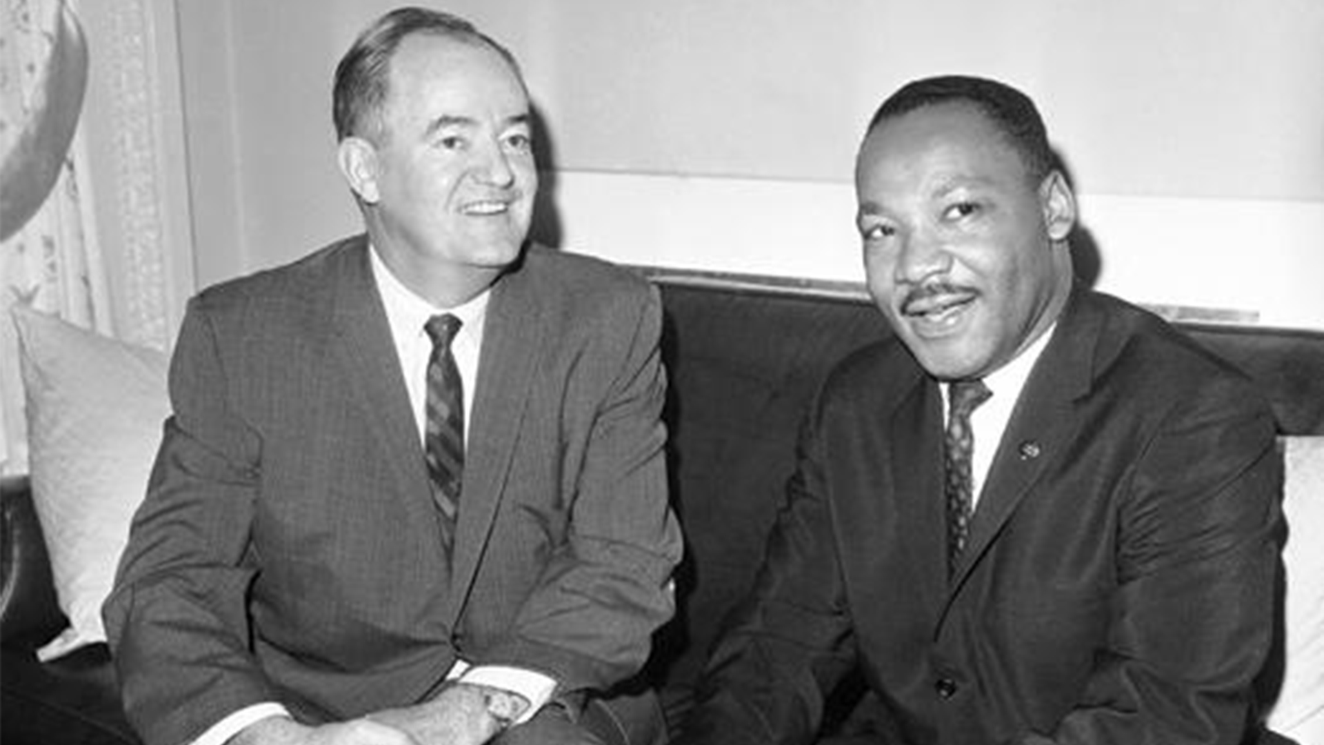 Hubert H. Humphrey and Martin Luther King Jr. sit together and smile at someone off-camera