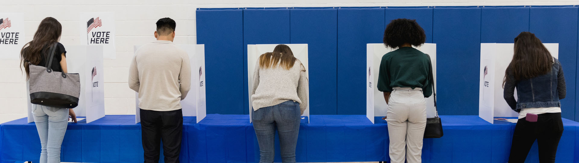 Long shot of several people voting at a polling place