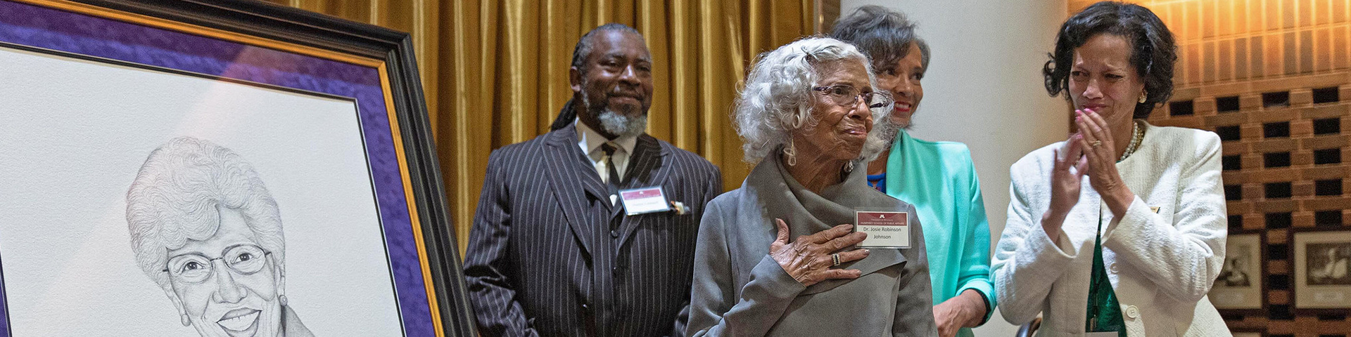 Josie Johnson views a portrait of her created for the dedication of the room at the Humphrey School that bears her name. Three people stand in the background smiling.