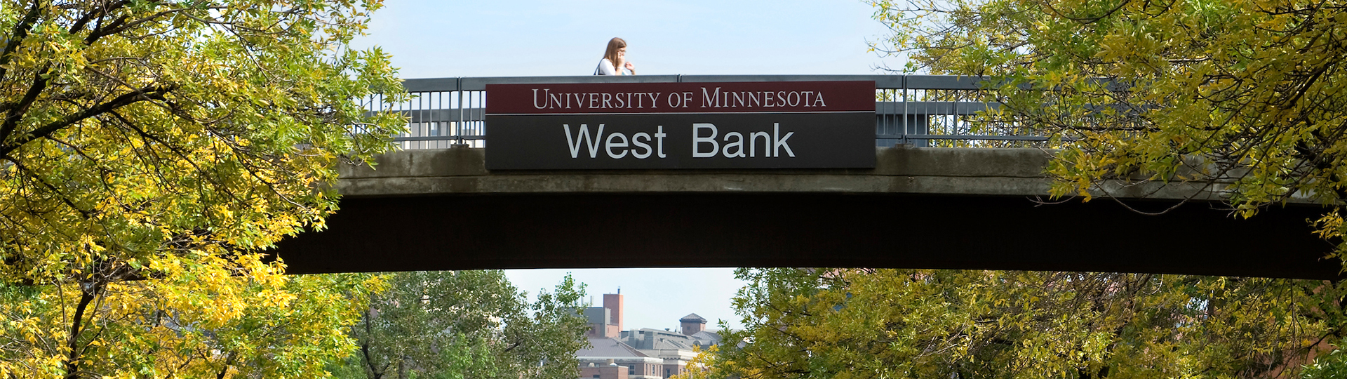 "A student walks across a footpath with a sign that reads ""University of Minnesota West Bank"""
