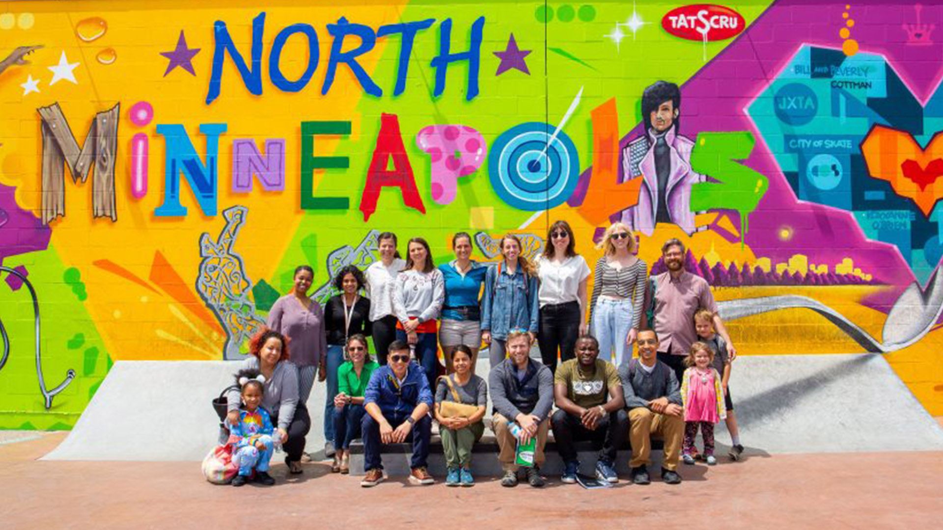 "A cohort from the CREATE Initiative poses in front of a colorful mural that says ""North Minneapolis"""