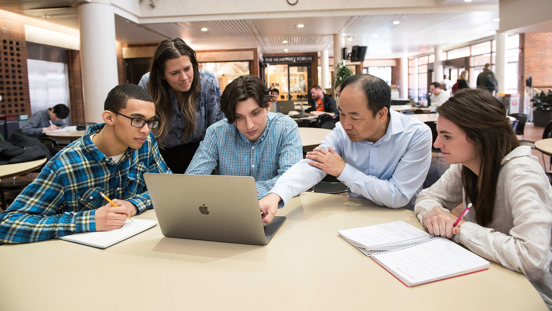 Four students and Professor Jerry Zhao look at a laptop screen