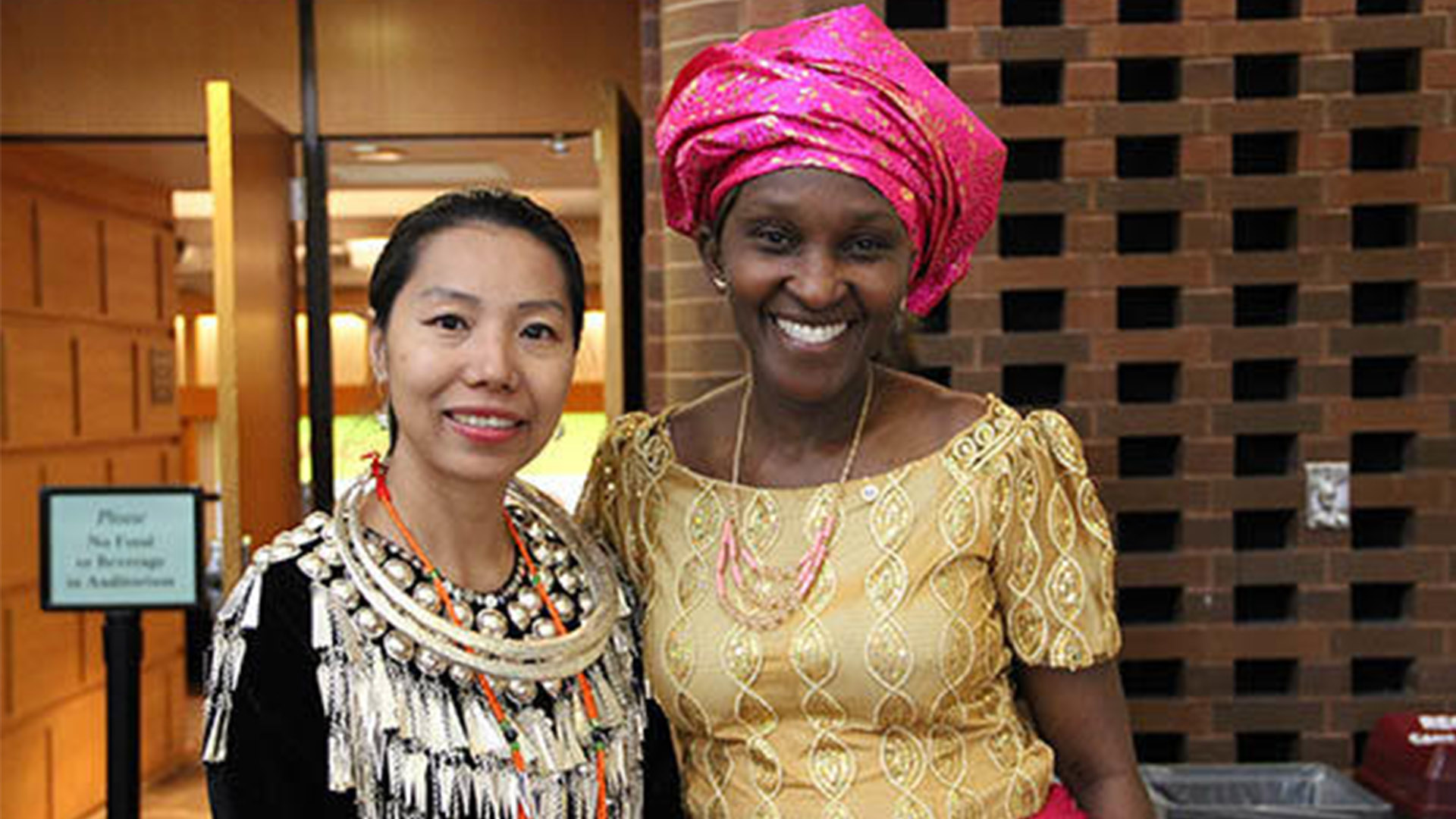 Two Humphrey School International Fellows pose in traditional clothing outside Cowles Auditorium