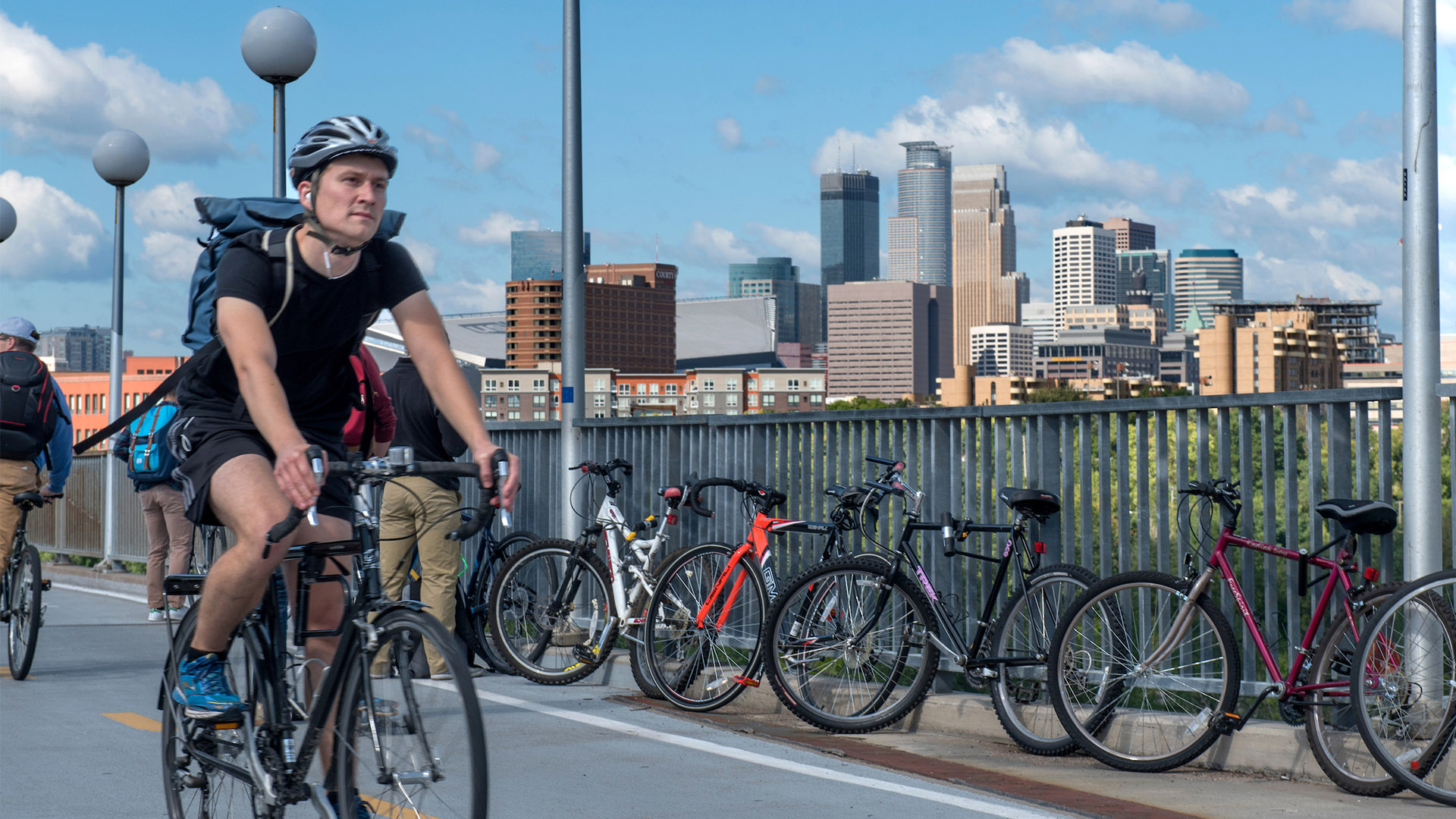 A student in a black shirt and shorts bikes down the Washington Avenue Bridge, with the Minneapolis skyline in the background