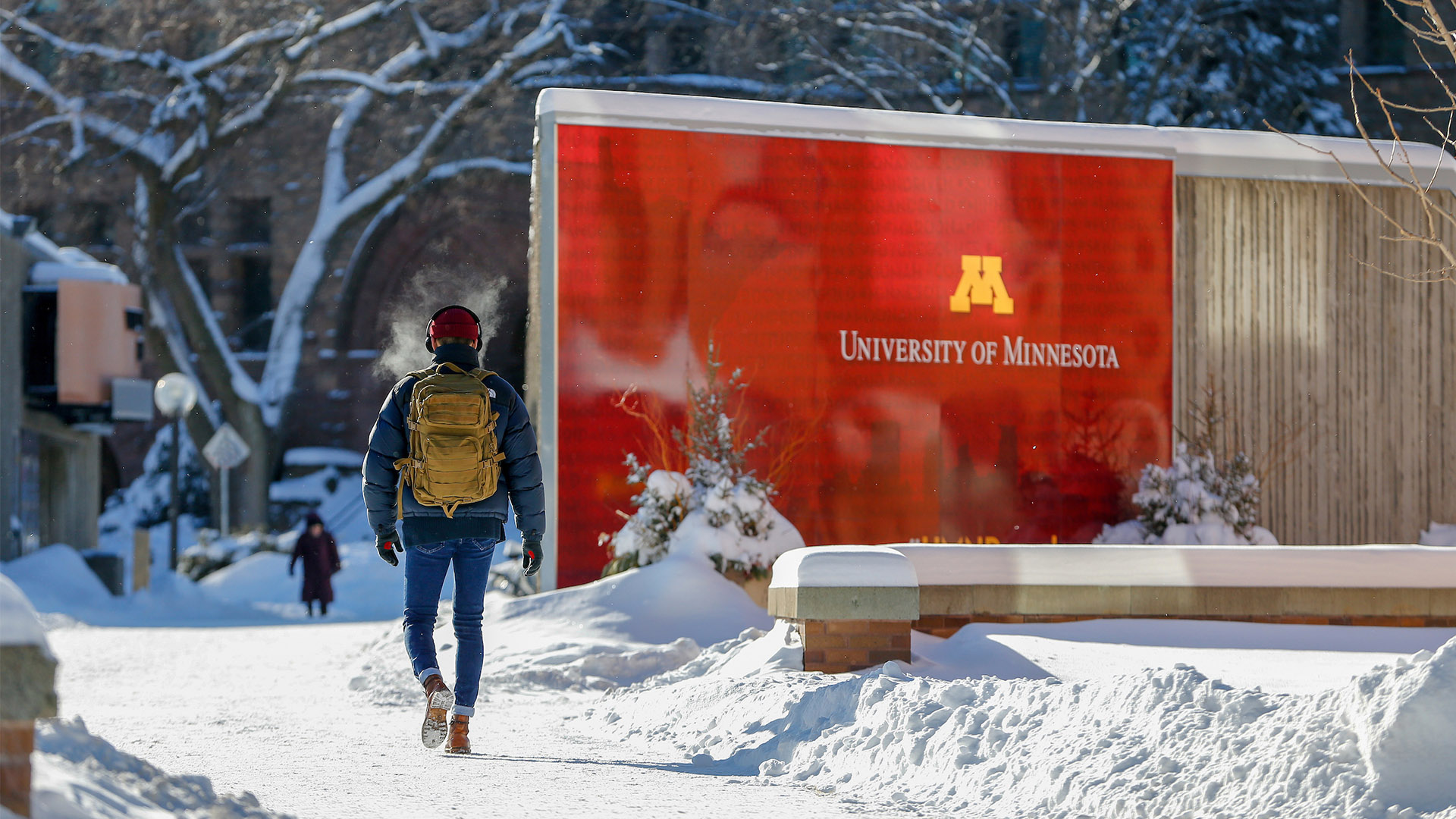 A student walks past a U of M sign on a snowy campus