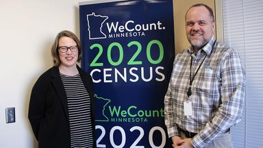 Alumni Susan Brower and Andrew Virden stand near a Census poster