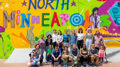 Group shot of CREATE researchers in front of a North Minneapolis mural