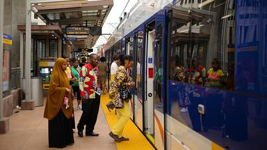 Commuters enter a light rail train at a station in Minneapolis