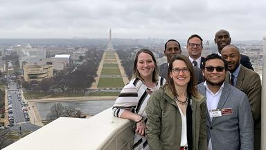 A group of policy fellows stand outside the US Capitol dome