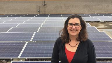 Headshot of Julia Nerbonne in front of a field of solar panels