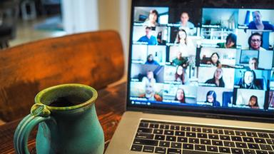 A mug of coffee sits next to a laptop with people on a Zoom call