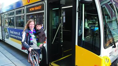 Woman holds a small child standing outside the door of a Metro Transit bus
