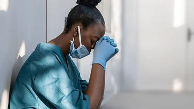 Health care worker leaning against a wall