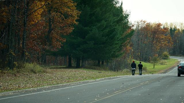 Two pedestrians walk on the shoulder of a rural highway