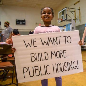 Child holds a sign saying 'we want more public housing'