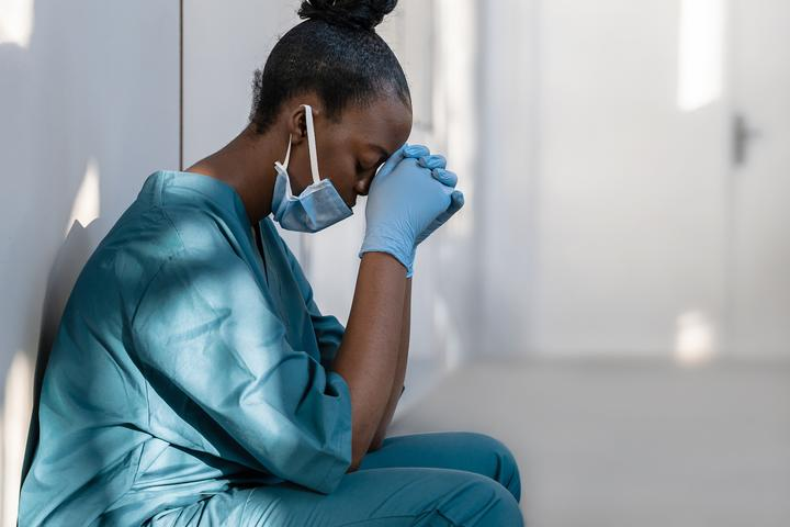 A female health care worker in a mask and scrubs, leaning against a wall